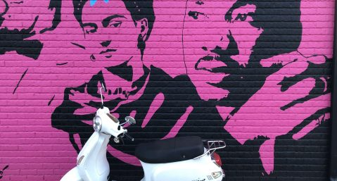A white motor scooter in front of a pink mural